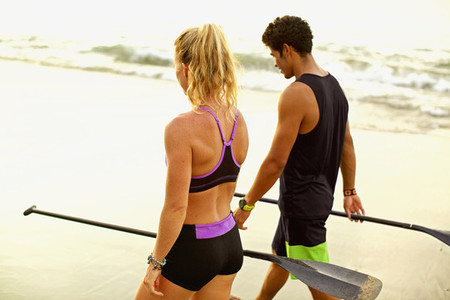 Young fit couple with oars walking on beach 01