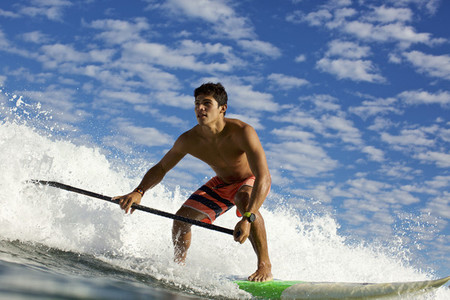 Young man on paddleboard riding ocean wave 01