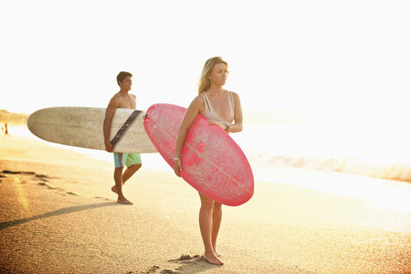 Young couple with surfboards walking on sunny beach 01