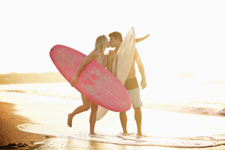 Young affectionate couple with surfboards kissing on sunny ocean beach 01