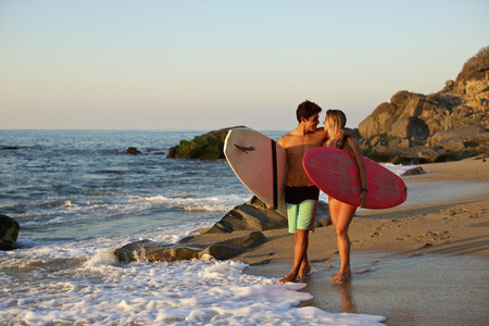 Young affectionate couple with surfboards walking on sunny ocean beach 01