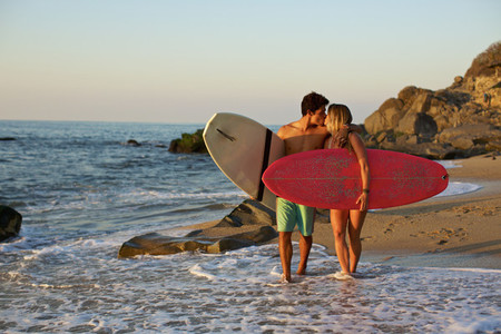 Young affectionate couple with surfboards walking on sunny ocean beach 02