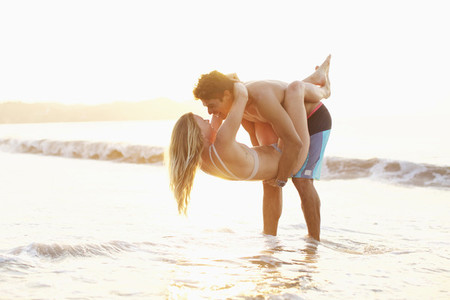 Playful affectionate young couple wading in ocean 01