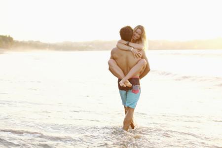 Boyfriend carrying girlfriend in ocean surf 01