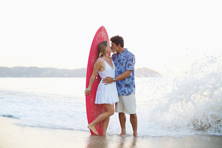 Affectionate couple with surfboard kissing on ocean beach 01