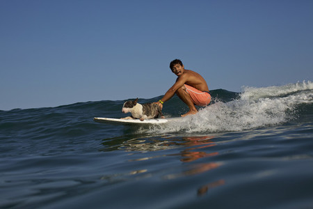 Portrait playful young man and dog riding surfboard on ocean wave 01