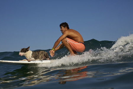 Young man and dog riding surfboard on ocean wave 01