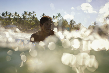 Young man swimming in sunny tropical ocean 01