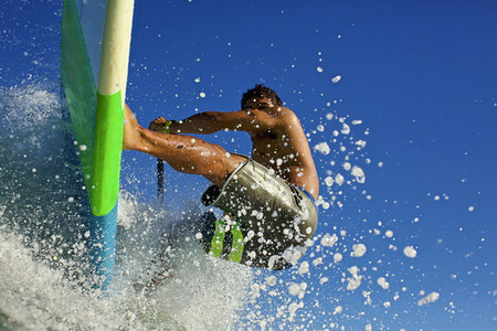 Young man riding paddleboard on ocean wave 01