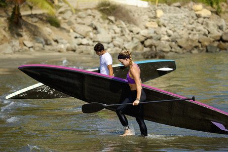 Young couple with paddleboards wading in ocean 01