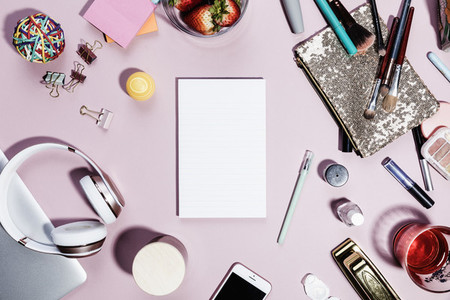View form above blank notepad surrounded by personal belongings on pink background 01