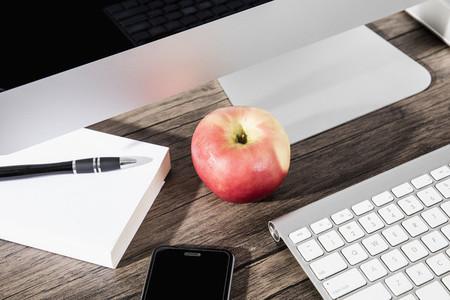 Apple and smart phone on desk below computer 01