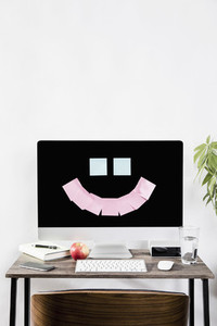 Adhesive notes forming smiley face on computer in office 01