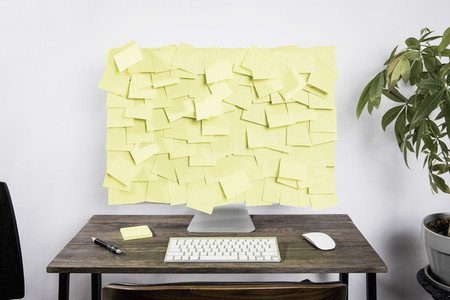 Adhesive notes covering computer on desk in office 01