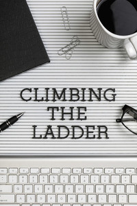 View form above Climbing the Ladder text on desk above computer keyboard 01