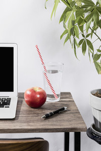 Water apple and pen on desk next to laptop in office 01