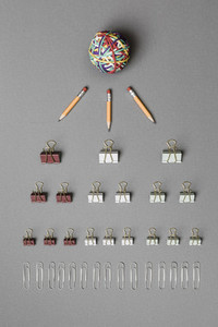 View form above rubber band ball pencils binder clips and paper clips on gray background 01