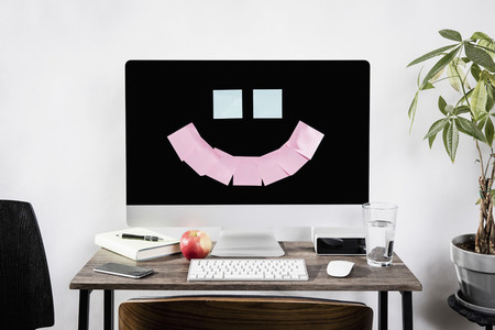 Adhesive notes forming smiley face on computer 01