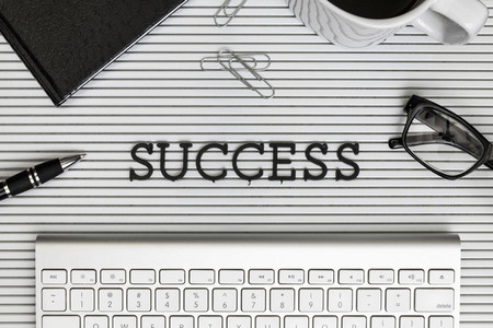 View form above Success text above computer keyboard on desk 01