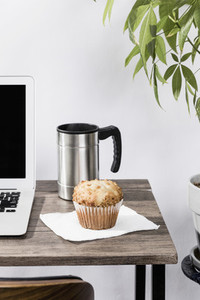 Insulated coffee mug and muffin on desk next to laptop in office 01