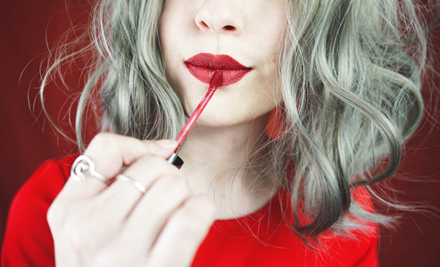 Young woman makeup her lips with a red matte lipstick