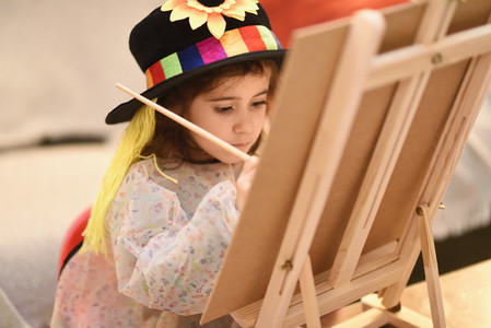 Little girl painting a picture at home