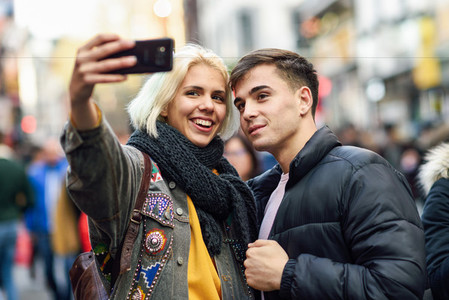 Happy couple of tourists taking selfie in a crowded street