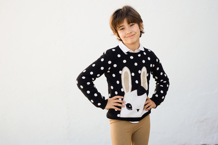 Seven years old girl with short hair smiling on a white wall