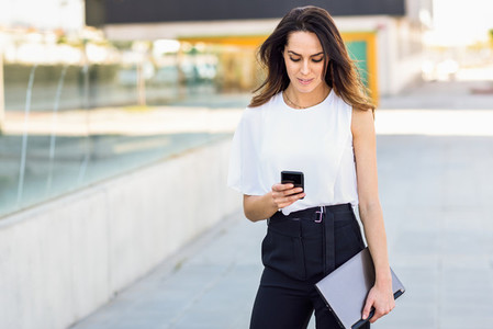 Middle aged businesswoman working with her smart phone and laptop outdoors