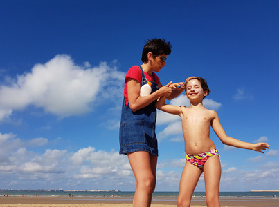 Mother throwing sunscreen on her little daughter