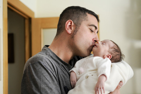 Father kissing his newborn baby girl