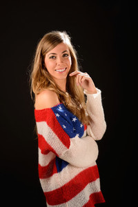 Beautiful blonde girl wearing a sweater with the flag of United