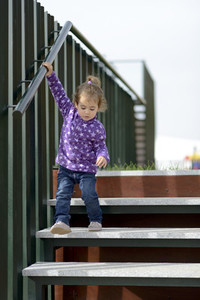Little girl going down some stairs outdoors