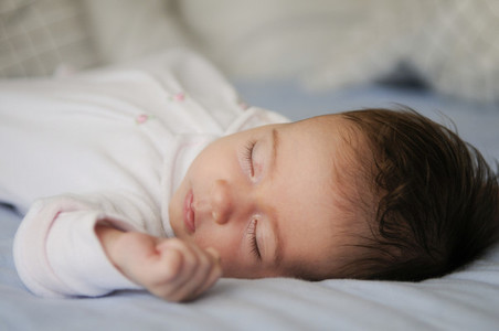 Newborn baby girl sleeping on blue sheets