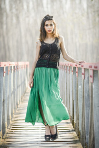 Woman wearing long dress in a rural bridge
