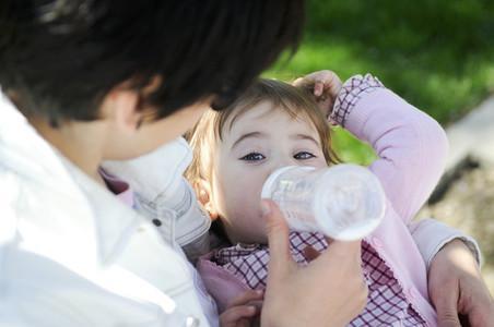 Mother feeding daughter from bottle