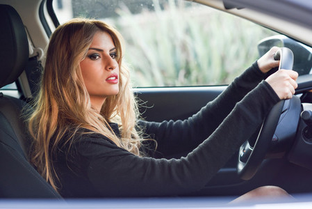 Blondie young woman driving a sport car