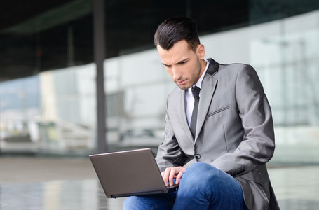 Young businessman typing in a laptop computer in urban backgroun