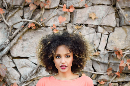Black woman with afro hairstyle standing in an urban park