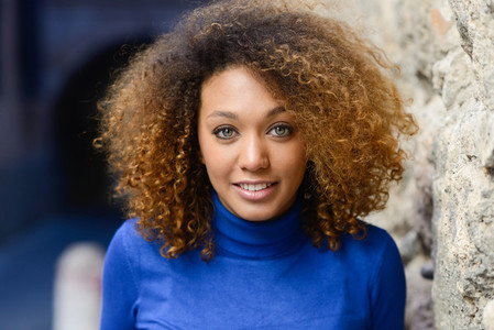 Young girl with afro hairstyle smiling in urban background