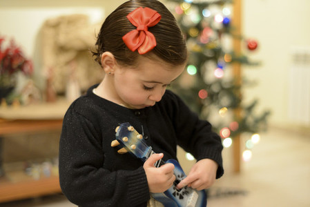 Little girl at home with decoration and defocused Christmas ligh