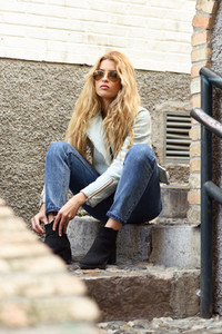 Beautiful young woman with curly hair wearing sunglasses