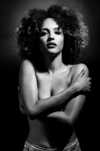 Young black woman with afro hairstyle on black background