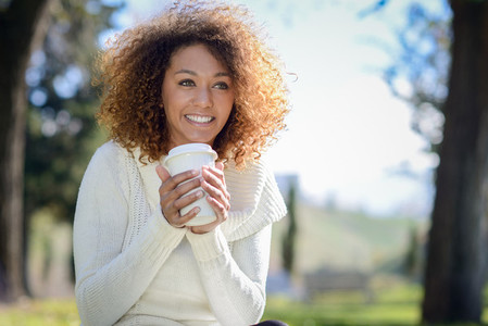 Young African American girl with afro hairstyle with coffee cup