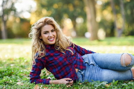 Beautiful woman with long blond curly hair in a park