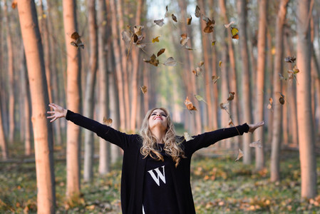 Happy woman playing with autumn leaves in forest