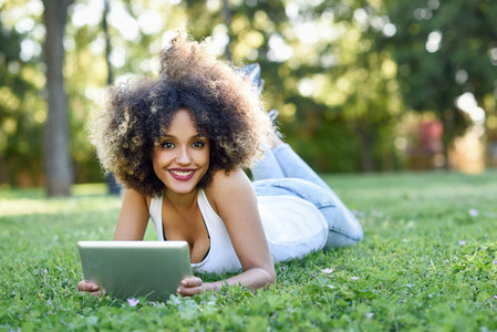 Mixed woman with afro hairstyle looking at her tablet computer