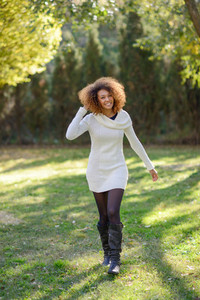 Young girl with afro hairstyle walking in an urban park