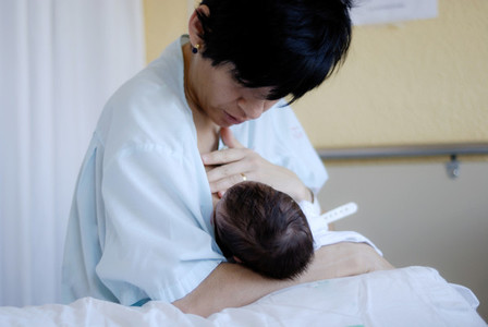Mother feeding breast her newborn baby at the hospital