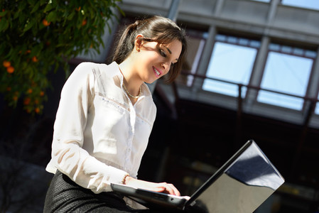 Attractive young businesswoman typing in a laptop computer urba